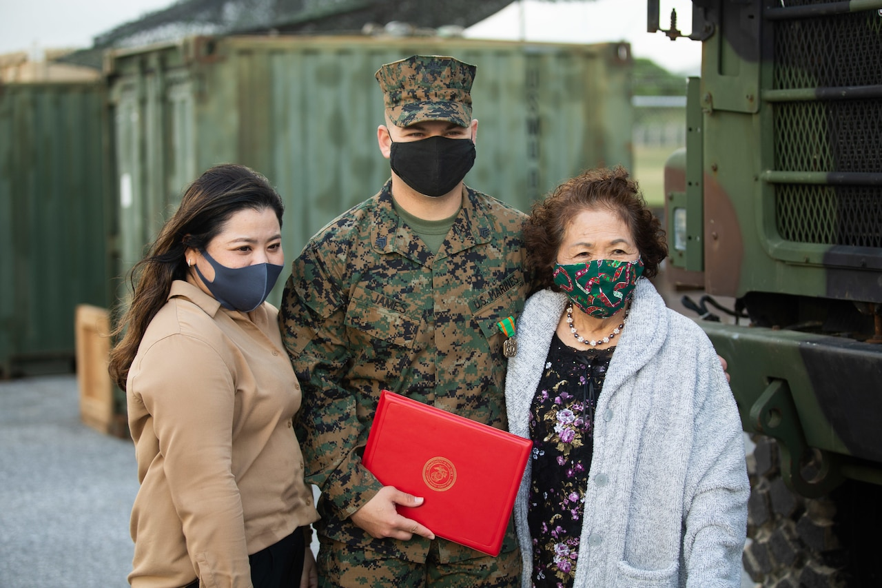 A Marine stands with two women.