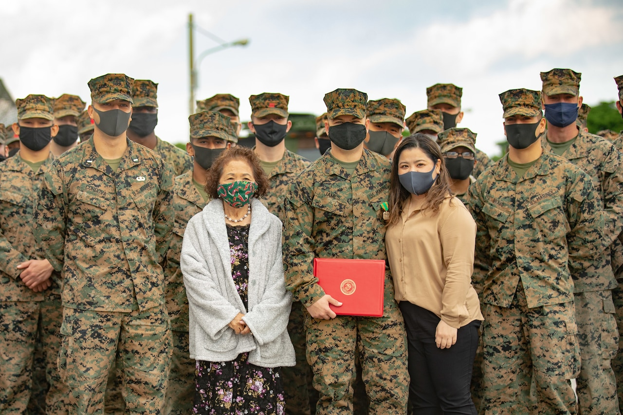 Marines stand with two women.