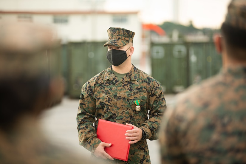A Marine wearing a medal holds a red folder.