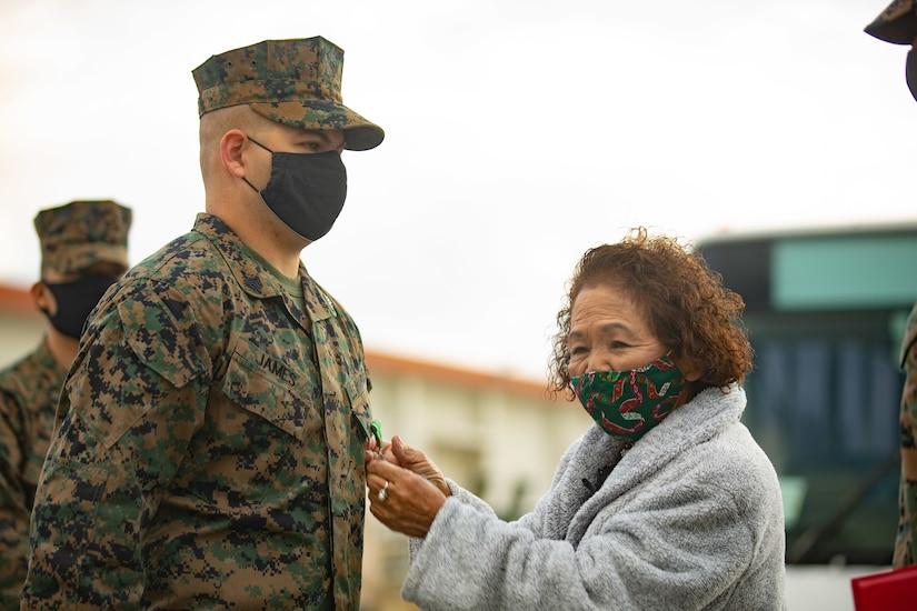 A woman pins a medal on a Marine.