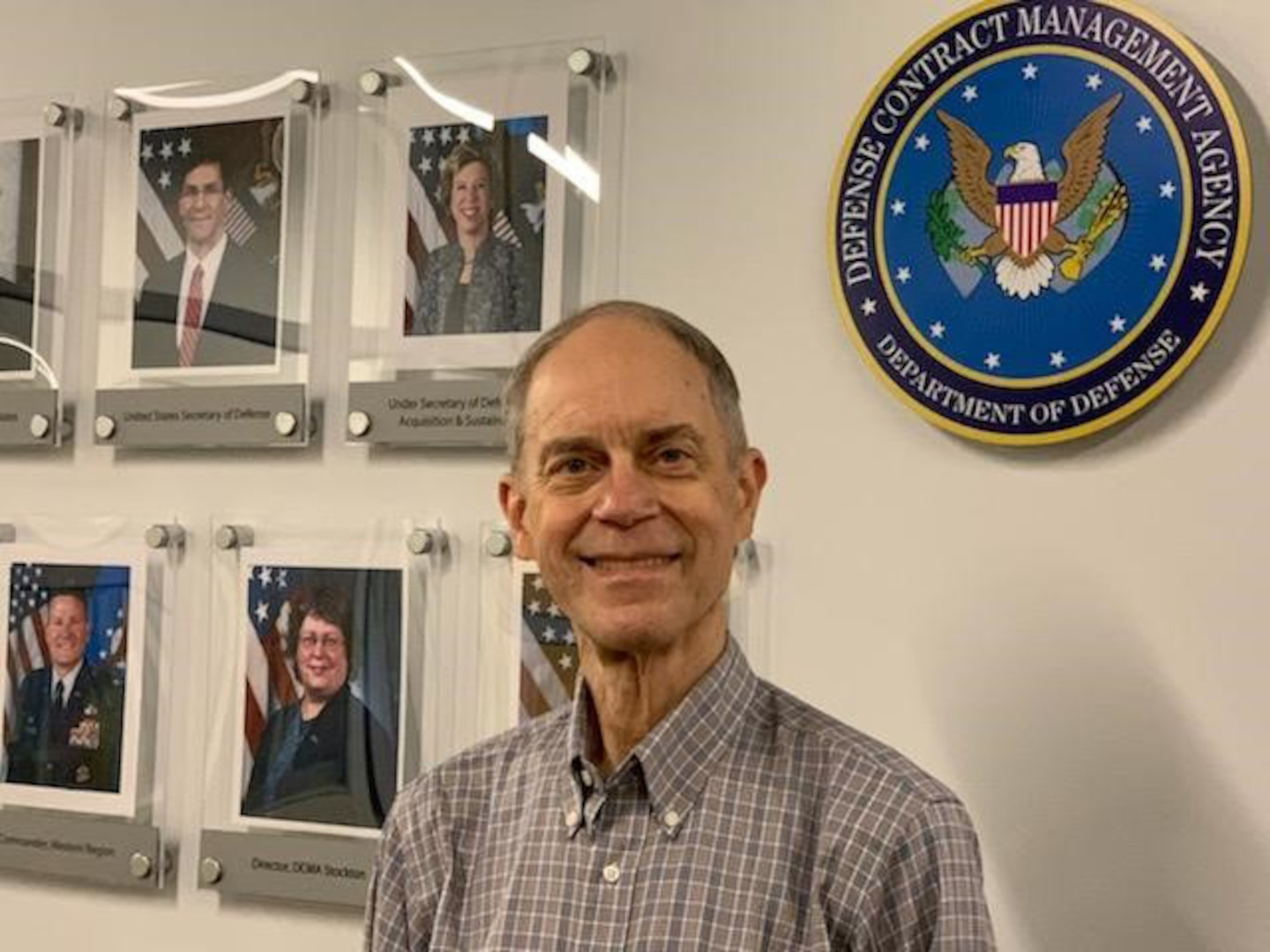A man stands in an office hallway with a wall of portraits behind him