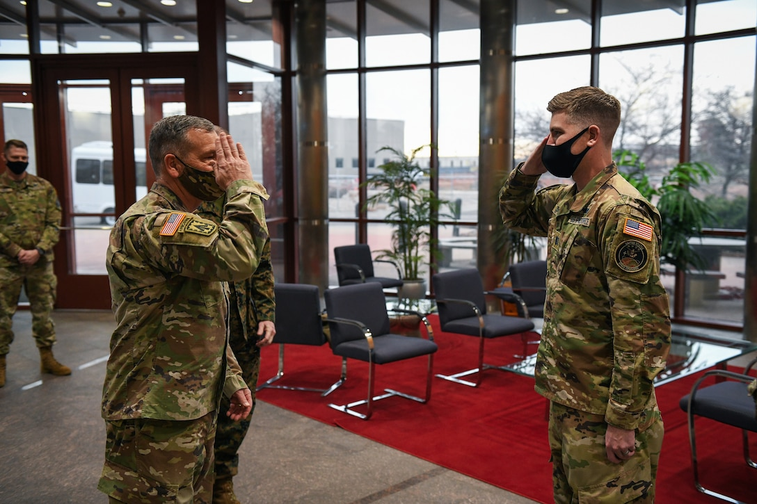 U.S. Army Gen. James Dickinson, left, U.S. Space Command commander, returns the salute of U.S. Space Force Capt. Peter Spittler, a 2nd Space Warning Squadron flight commander, after coining Spittler in the Mission Control Station lobby on Buckley Air Force Base, Colo., Jan 7, 2021.