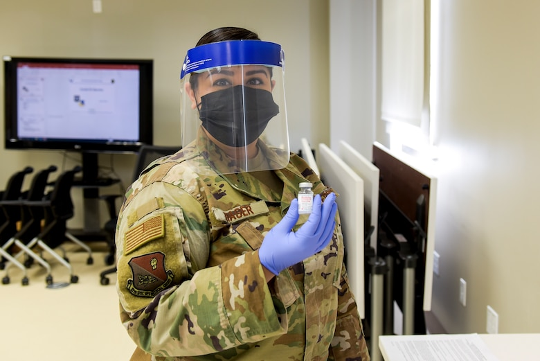 Staff Sgt. Melissa Hager, 27th Special Operations Medical Group immunizations clinic non-commissioned-officer-in-charge, holds up the COVID-19 vaccine that will be administered to active duty members at Cannon Air Force Base, N.M., Jan. 7, 2021. The vaccine distribution was handled by multiple members of the 27 SOMDG to ensure it was safely and properly delivered. (U.S. Air Force photo by Senior Airman Vernon R. Walter III)