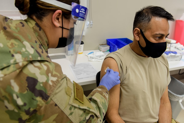 Staff Sgt. Melissa Hager, 27th Special Operations Medical Group immunizations clinic non-commissioned-officer-in-charge, swabs the arm of Col. Sanjay Gogate, 27 SOMDG commander, before administering the COVID-19 vaccine to him at Cannon Air Force Base, N.M., Jan. 7, 2021. During the process, members were given briefings before and after receiving their shots to help answer questions. (U.S. Air Force photo by Senior Airman Vernon R. Walter III)