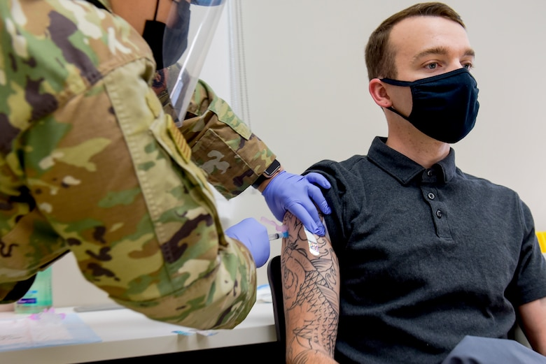 A member of the 27th Special Operations Security Force Squadron receives a COVID-19 vaccine from Staff Sgt. Melissa Hager, 27th Special Operations Medical Group immunizations clinic non-commissioned-officer-in-charge. 20 personnel were given the vaccine with more planned in the following days. (U.S. Air Force photo by Senior Airman Vernon R. Walter III)