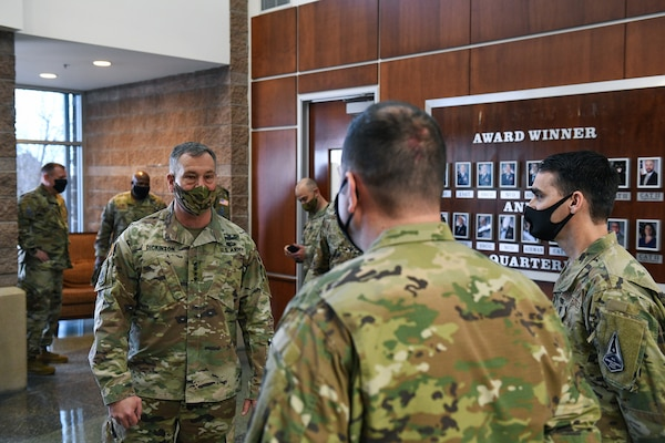 Chaplain (Maj.) Justin Combs, right, introduces Tech. Sgt. Matthew Brandt, center, Buckley Garrison Staff Agencies NCO in charge of training and readiness, prior to U.S. Army Gen. James Dickinson, left, U.S. Space Command commander, coining Brandt for exceptional performance in the Headquarters building on Buckley Air Force Base, Colo., Jan. 7, 2021.
