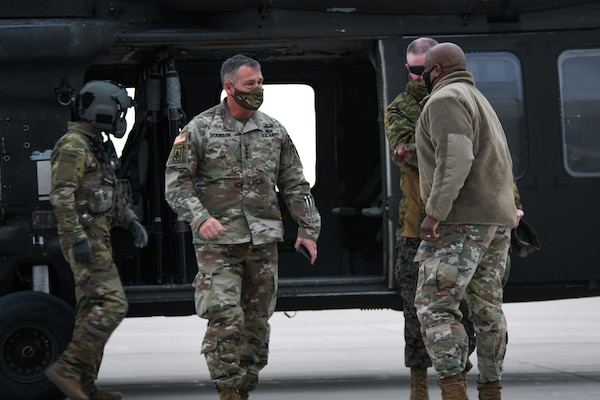 U.S. Army Gen. James Dickinson, left, U.S. Space Command commander, and U.S. Marine Corps Master Gunnery Sgt. Scott H. Stalker, USSPACECOM senior enlisted leader, are greeted by U.S. Air Force Col. Devin Pepper, far right, Buckley Garrison commander, on the flightline on Buckley Air Force Base, Colo., Jan. 7, 2021.