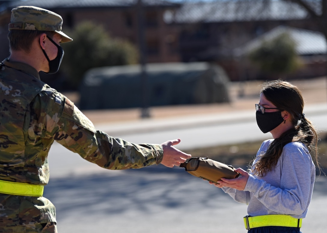 U.S. Air Force Airman Silas Poock, 316th Training Squadron student, hands a goody bag to an Airman during the distribution of donated goods from the USO at the Cressman Dining Facility on Goodfellow Air Force Base, Texas, Jan. 7, 2021. The bags were filled with a variety of candy, and snacks members could enjoy in their dorms. (U.S. Air Force photo by Airman 1st Class Ethan Sherwood)