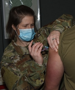 Senior Airman Sara Basiliere injects Spc. Bareden Langmaid with a dose of COVID-19 vaccine during the Vermont National Guard's vaccine rollout at Camp Johnson, Vermont, Jan. 7, 2021. Langmaid, a construction equipment repair specialist with Echo Company, 5-72nd Brigade Engineer Battalion, said he received the shot to help mitigate his COVID-19 risk while he works on sample testing. Basiliere is an immunology specialist with the Vermont Air National Guard's 158th Medical Group.