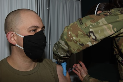 Capt. Lewis Lizotte receives a dose of COVID-19 vaccine from Lt. Col. Sarah Davis during the Vermont National Guard's vaccine rollout Jan. 7, 2021, at Camp Johnson, Vermont. Lizotte, who is assigned to Joint Force Headquarters Vermont but is currently working as a contact tracer, said he volunteered to receive the shot to protect his family. Davis is a registered nurse and the officer in charge of immunizations for the Air National Guard's 158th Medical Group.