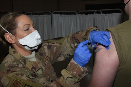Air Force Lt. Col. Amber Macrae injects Air Force Tech. Sgt. Eric Boudro with a dose of COVID-19 vaccine during the Vermont National Guard's vaccine rollout Jan. 7, 2021, at Camp Johnson, Vermont. Boudro, a security forces NCO with the Air National Guard's 158th Security Forces Squadron, said he is getting the vaccine to protect his loved ones. Macrae is a nurse anesthesist with the Vermont Air National Guard's 158th Medical Group.