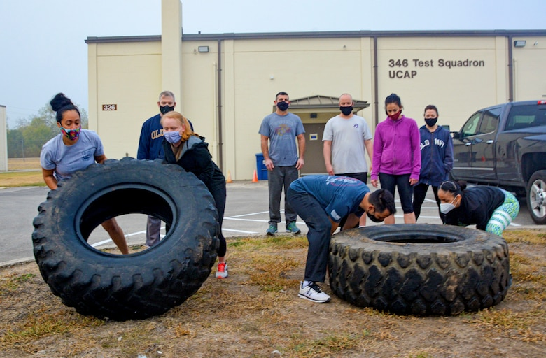 First sergeants of the 960th Cyberspace Wing lift tires Nov. 19, 2020, in a team building exercise during the wing leadership summit at Joint Base San Antonio-Chapman Training Annex, Texas. (U.S. Air Force photo by Samantha Mathison)