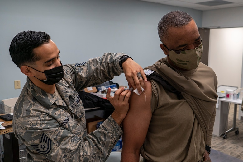 U.S. Air Force Reserve Technical Sgt. Franklin Cordon a medical technician with the 78th Healthcare Operations Squadron, administers the Covid-19 vaccine to Chief Master Sgt. Timothy White, senior enlisted advisor to the chief of the Air Force Reserve and command chief, Air Force Reserve Command, January 8th, 2021 at Robins Air Force Base, GA. (US Air Force photo by Technical Sgt. Nicholas A. Priest)
