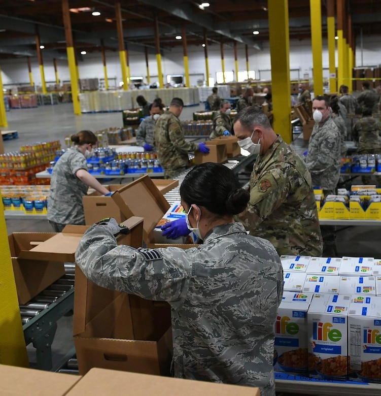 Air National Guardsmen prepare food boxes at the Food Lifeline Covid Response