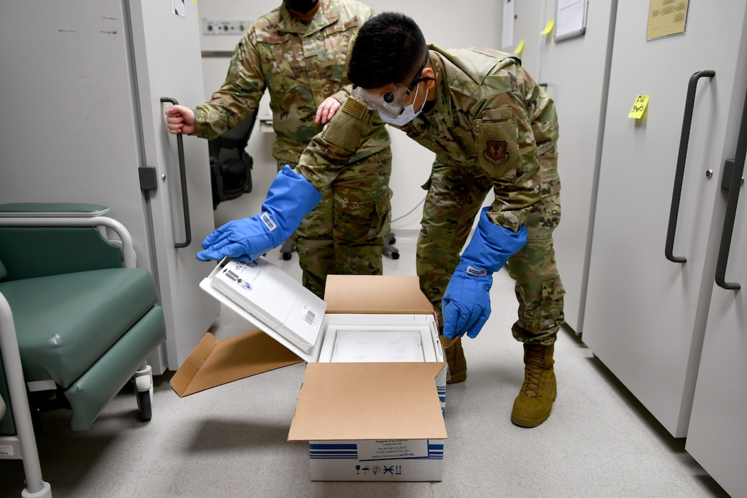 Senior Airman Siejeay Dimla, 31st Medical Support Squadron medical logistics technician, opens a case containing COVID-19 vaccines at Aviano Air Base, Italy, Jan. 7, 2021.