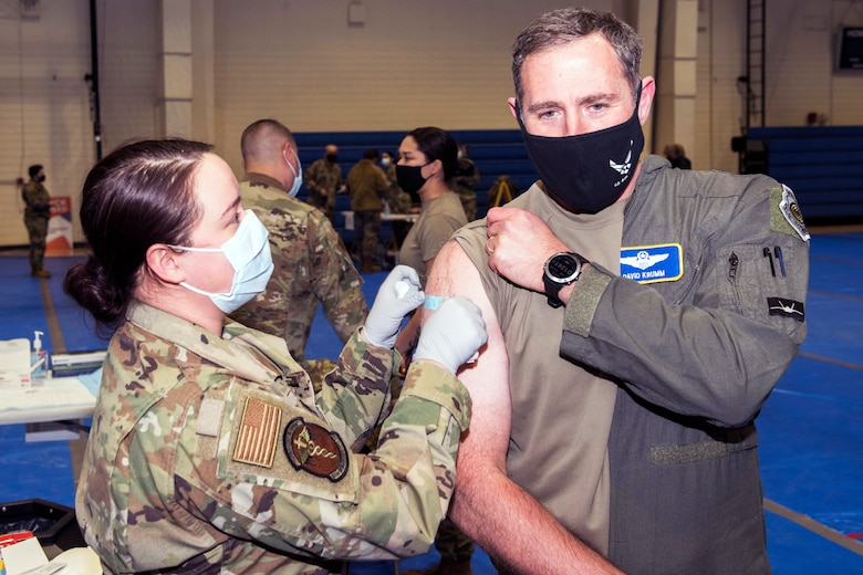 An airman gives a COVID-19 vaccine to a senior Air Force officer