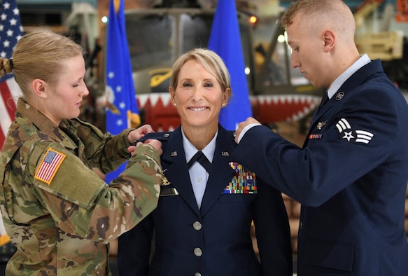 Cadet Tori Flarity and Senior Airman Patrick Flarity pin stars on their newly promoted mother, Brig. Gen. Kathleen Flarity, mobilization assistant to the command surgeon, Air Mobility Command, during a ceremony at Wings Over the Rockies Air and Space Museum, Denver, Colorado.