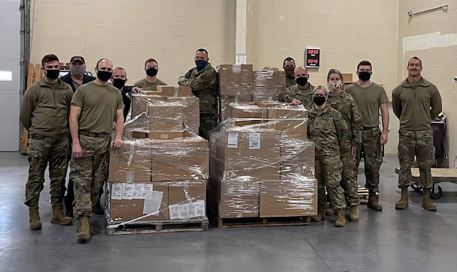 Members of the 185th Air Refueling Wing stand with some of the 11,342 pounds of food collected during the units annual food drive.