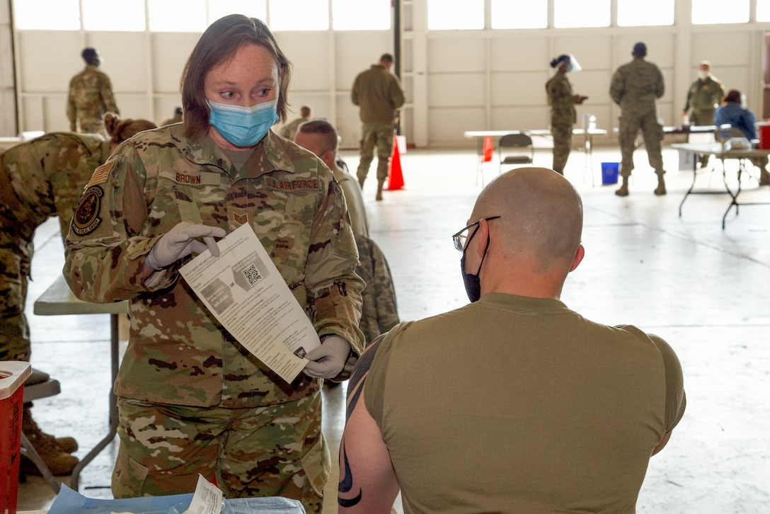 Tech. Sgt. Barbara Brown, 108th Wing Medical Group, displays a factsheet after administering the COVID-19 vaccine at Joint Base McGuire-Dix-Lakehurst, N.J., Jan. 9, 2021. This was the first time the 108th Wing administered the COVID-19 vaccines to wing members.
