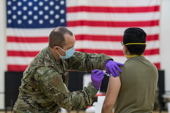 U.S. Air Force 2nd Lt. James Black, a clinical nurse with the 514th Aerospace Medicine Squadron, 514th Air Mobility Wing, administers a COVID-19 vaccine to Tech Sgt. David Bettetta, and optometry specialist with the 514 AMDS at Joint Base McGuire-Dix-Lakehurst, N.J., on Jan. 9, 2021.