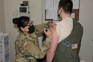 Technical Sgt. Perla Solis, 185th Air Refueling Wing medical technician, administers the first of two COVID-19 vaccines to an Airman from the Iowa Air National Guard at the Sioux City, Iowa, clinic on Jan. 9, 2021.
