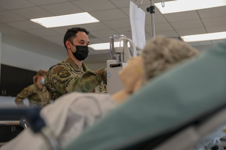 Image of a Service member helping a patient.