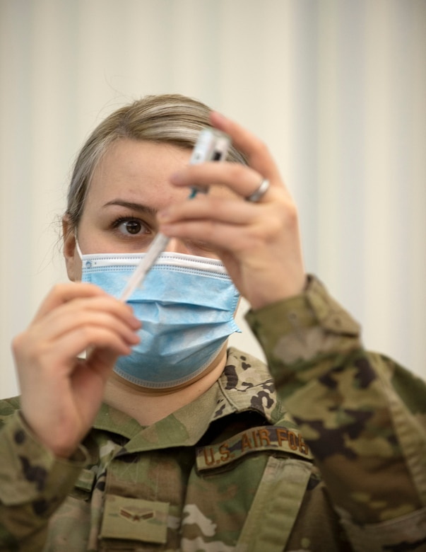 A member from the 133rd Medical Group prepares a syringe with the Moderna COVID-19 vaccine in St. Paul, Minn., Jan. 8, 2021.