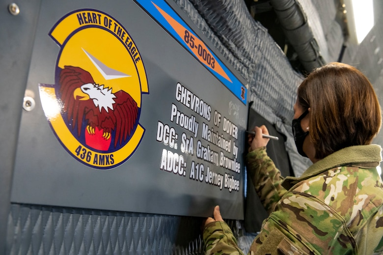 Chief Master Sgt. of the Air Force JoAnne S. Bass signs a plaque during a C-5M Super Galaxy static display walk-through Jan. 8, 2021, on Dover Air Force Base, Delaware. The office of the Chief Master Sergeant of the Air Force represents the highest enlisted level of leadership, provides direction for the enlisted corps and represents their interests to the American public and all levels of government. Dover is home to nearly 11,000 total force Airmen supporting 20% of the nation's strategic airlift capability.(U.S. Air Force photo by Senior Airman Christopher Quail)