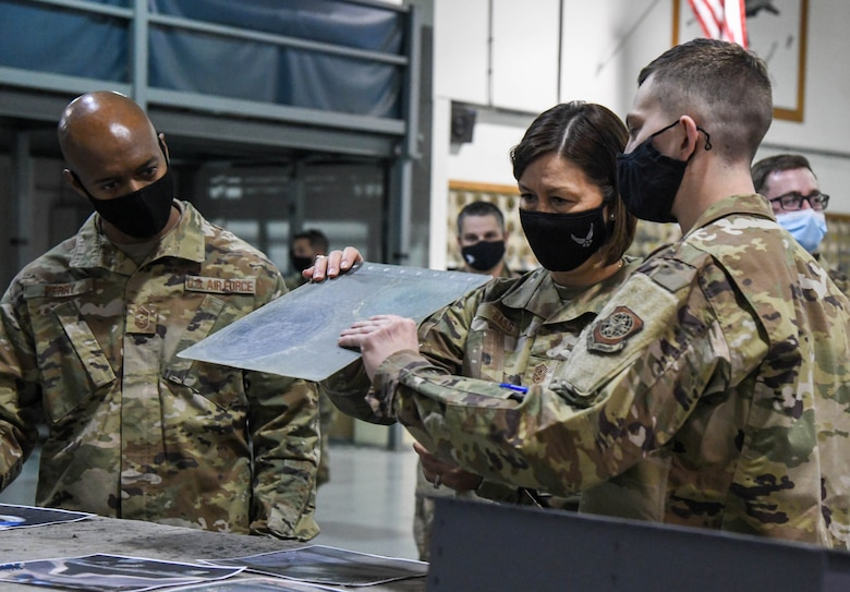 Senior Airman Donovan Lamore, 436th Maintenance Squadron aircraft structural maintenance apprentice, shows a metal sheet to Chief Master Sergeant of the Air Force JoAnne S. Bass, during her visit to Dover Air Force Base, Delaware, Jan. 8, 2021. Chief Bass witnessed firsthand how Dover AFB supports Air Force priorities such as enhancing full-spectrum readiness and developing innovative, multi-capable Airmen. (U.S. Air Force photo by Airman 1st Class Stephani Barge)