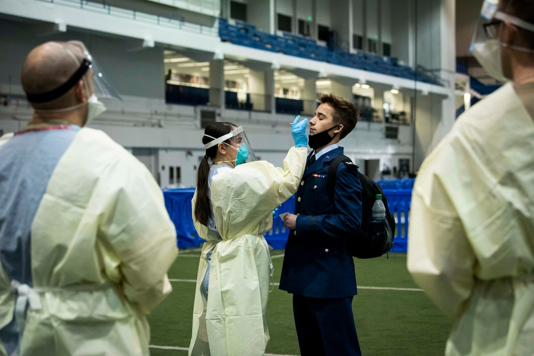An Air Force cadet is given a COVID-19 rapid test from medical personnel wearing personal protective equipment.