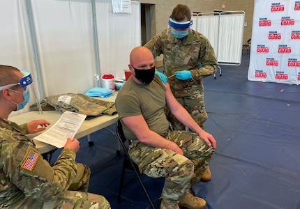 Indiana National Guard Sgt. Abigail Gates, a medic with 38th Infantry Division, administers a COVID-19 vaccination shot Dec. 16, 2020, in Franklin, Indiana, to Sgt. 1st Class Ben Cripe, an artilleryman. Hoosier Guardsmen have been critical to fighting the coronavirus pandemic, helping at food banks, distributing protective equipment, assisting long-term care facilities. They will now help distribute the coronavirus vaccine.</p>
