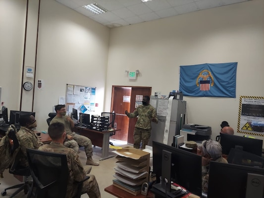 Air Force Senior Master Sgt. Samson McLester lead a Jan. 6 team meeting at DLA Disposition Services in Qatar to discuss an upcoming professional development seminar/morale & team building event.