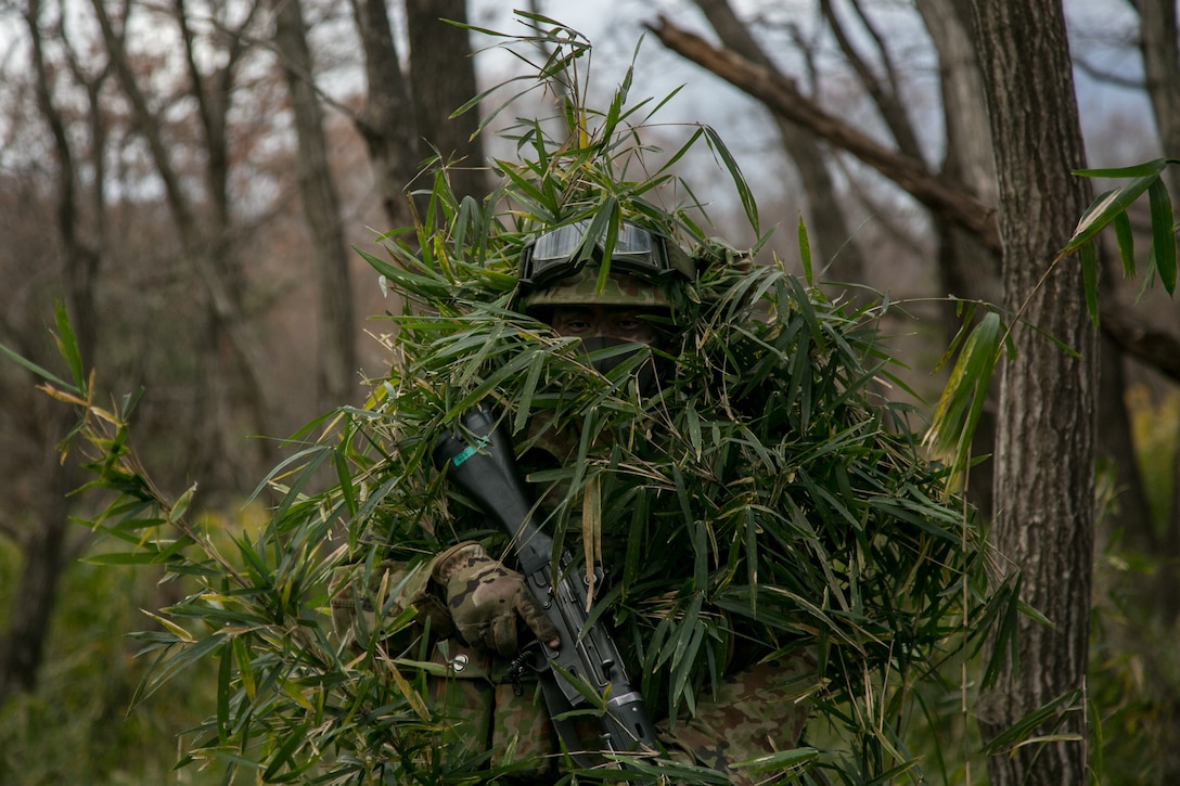 An infantryman from the 30th Infantry Regiment, 12th Brigade, Japan Ground Self-Defense Force conceals himself in mainland Japan, Dec. 14.