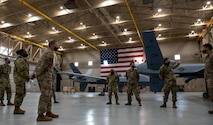 A group of Airmen stand in a hangar with an MQ-9 Reaper.