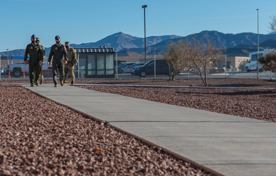 432nd Wing/432nd Air Expeditionary Wing leadership walks with Fifteenth Air Force leadership down a sidewalk.