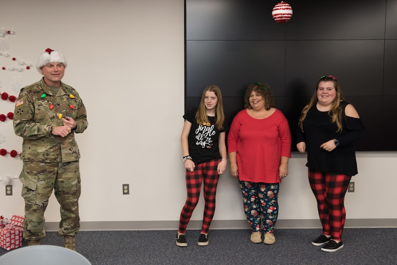 Robyn Ratchford, 20-year volunteer at the Middle East District, stands between her two daughters and major helpers following a successful 2019 holiday party for the District, while TAM Commander COL Philip Secrist in holiday garb, applauds their efforts, ingenuity, and creativity. Ratchford is the backbone and heavy muscle of the District's Employees Activities Association.