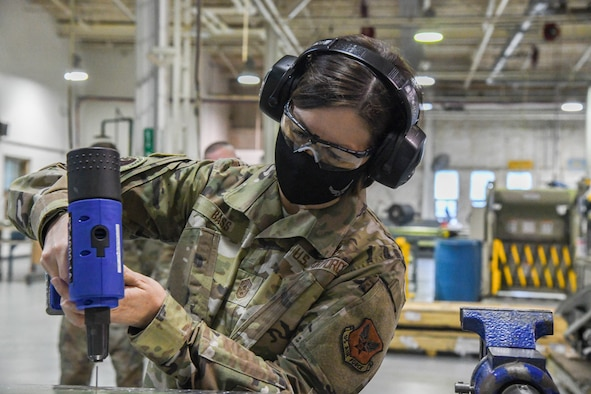 Chief Master Sergeant of the Air Force JoAnne S. Bass learns how to use an air compressed nail gun during her visit to Dover Air Force Base, Delaware, Jan. 8, 2021. The office of the Chief Master Sergeant of the Air Force represents the highest enlisted level of leadership, provides direction for the enlisted corps and represents their interests to the American public and all levels of government. (U.S. Air Force photo by Airman 1st Class Stephani Barge)