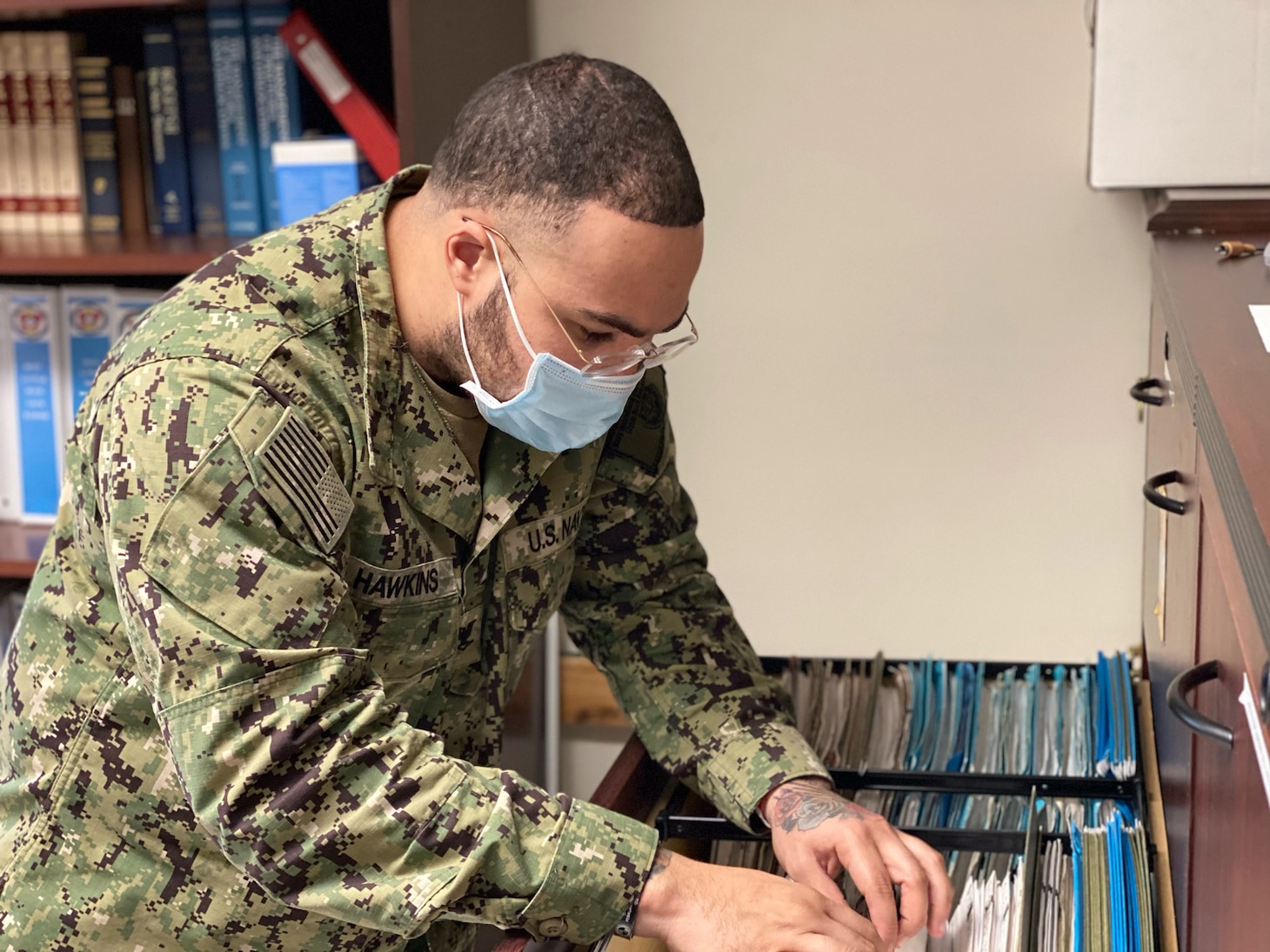 LITTLE ROCK, Arkansas (Jan. 9, 2021) - Damage Controlman 3rd Class Dante Hawkins, assigned as a Medical department representative at Navy Operational Support Center (NOSC) Little Rock, pulls a medical record while conducting physical health assessments of Selected Reservist (SELRES) Sailors during NOSC Little Rock's first drill weekend of the year. In its effort of taking a more streamlined approach to warfighting readiness in accordance with the Chief of Navy Reserve's recently released Fighting Instructions, NOSC Little Rock contucted tailored training, performed medical readiness examinations and immunizations, and facilitated establishing communication between SELRES Sailors and their cross-assigned in units. (U.S. Navy photo taken by Electronics Technician 1st Class Stephen Landry/Released)