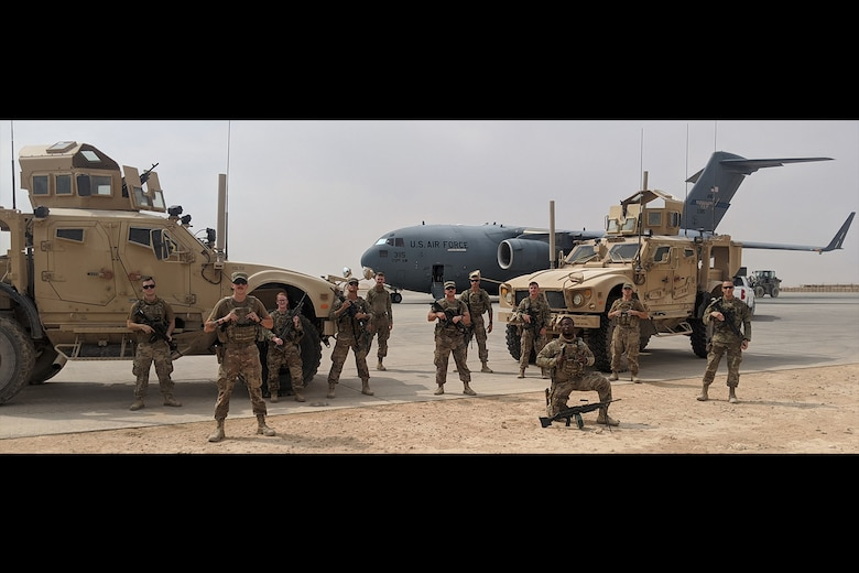 Photo shows military members standing in front of two humvees and a C-17 aircraft in the desert.