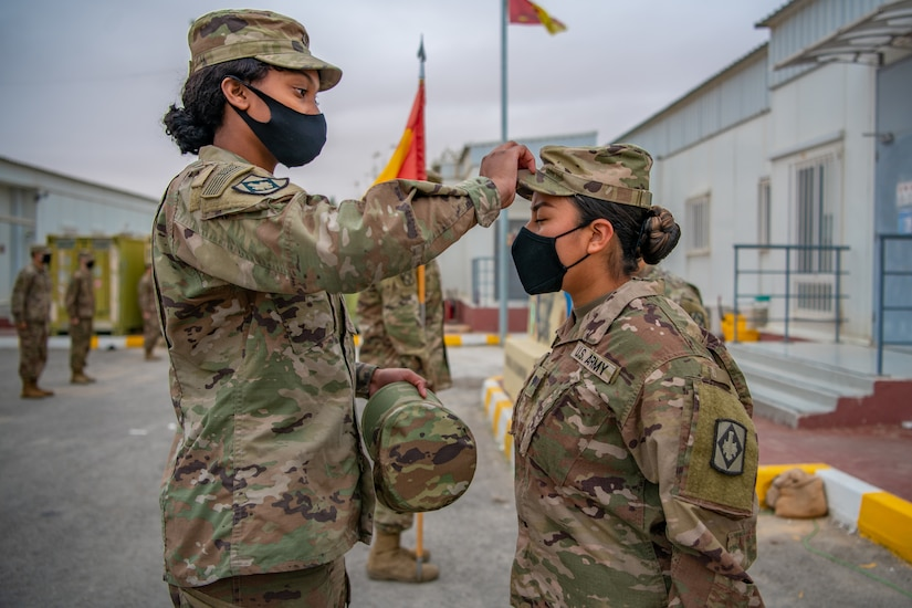 Pfc. Tiffany Miles, left, the unit supply specialist for Headquarters and Headquarters Battery, 75th Field Artillery Brigade, Fort Sill, OK, swaps Sgt. Brandy Lopez, right, an Information Technology (IT) Specialist assigned to 75th Field Artillery Brigade, patrol cap with on displaying her new rank while deployed to the Middle East on December 28, 2020. For the past nine months, Lopez had provided countless hours of IT support and troubleshooting to every Diamond Brigade Soldier deployed to the Middle East and was selected as the only Specialist to be promoted through Battle Field Promotion within Area Support Group - Jordan. (U.S. Army photo by Sgt. Dustin D. Biven / 75th Field Artillery Brigade)