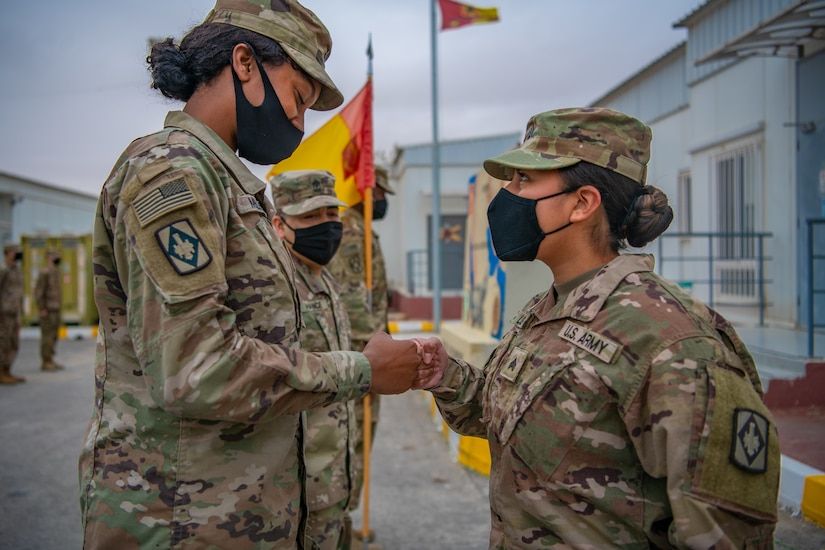 Pfc. Tiffany Miles, left, the unit supply specialist for Headquarters and Headquarters Battery, 75th Field Artillery Brigade, Fort Sill, OK, congratulates Sgt. Brandy Lopez, right, an Information Technology (IT) Specialist assigned to 75th Field Artillery Brigade, on her recent promotion while deployed to the Middle East on December 28, 2020. For the past nine months, Lopez had provided countless hours of IT support and troubleshooting to every Diamond Brigade Soldier deployed to the Middle East and was selected as the only Specialist to be promoted through Battle Field Promotion within Area Support Group - Jordan. (U.S. Army photo by Sgt. Dustin D. Biven / 75th Field Artillery Brigade)