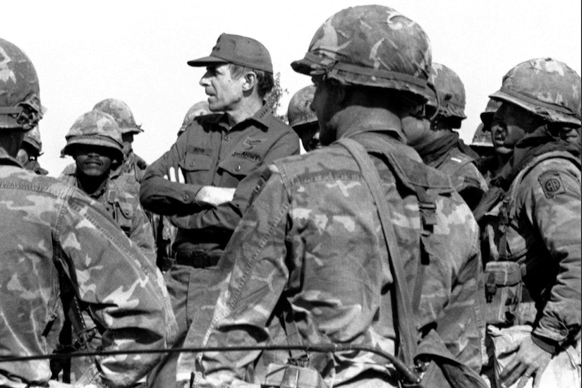 A man wearing a military uniform stands elevated as he talks to soldiers.