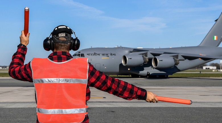 A member of the 436th Aircraft Maintenance Squadron transient alert marshals an Indian air force C-17 Globemaster III Nov. 20, 2020, at Dover Air Force Base, Delaware. Dover AFB annually supports $3.5 billion worth of FMS operations due to its strategic location and 436th Aerial Port Squadron, the largest aerial port in the Department of Defense. The United States and India have shared interests in promoting global security, stability and economic prosperity. (U.S. Air Force photo by Senior Airman Christopher Quail)