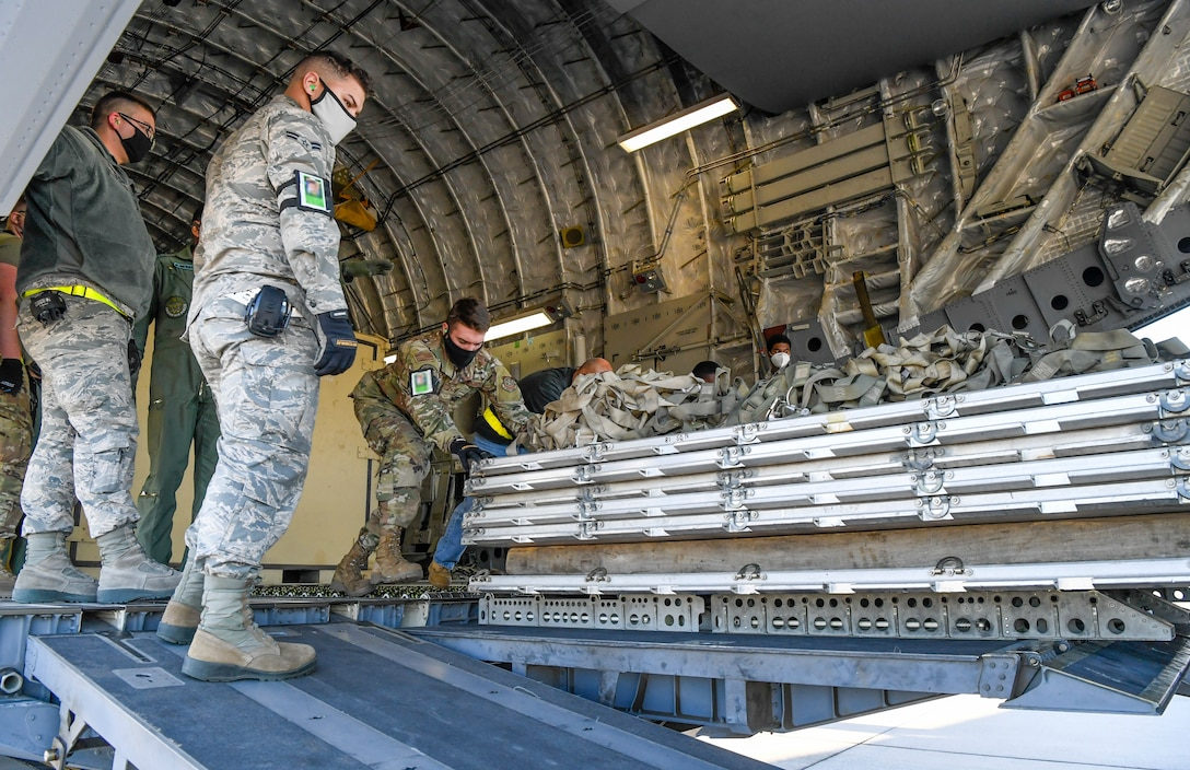 Airmen from the 436th Aerial Port Squadron unload cargo from an India air force C-17 Globemaster III at Dover Air Force Base, Delaware, Nov. 20, 2020. Dover AFB annually supports $3.5 billion worth of FMS operations due to its strategic location and 436th Aerial Port Squadron, the largest aerial port in the Department of Defense. The United States and India have shared interests in promoting global security, stability and economic prosperity. (U.S. Air Force photo by Senior Airman Christopher Quail) (This image was altered for security purposes by blurring identification badges)