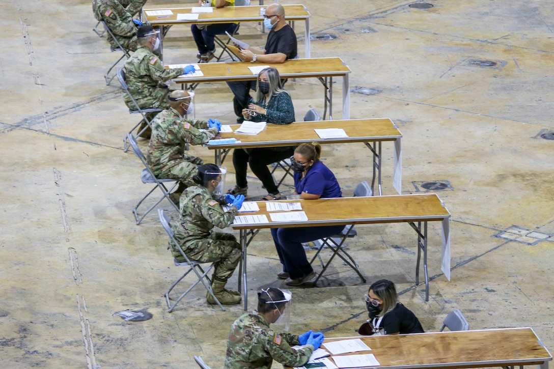 An aerial photograph shows a person wearing a military uniform sitting at each of six tables lined up outside; a person wearing civilian clothing sits opposite each service member. Pieces of paper are on the tables in front of the service members.