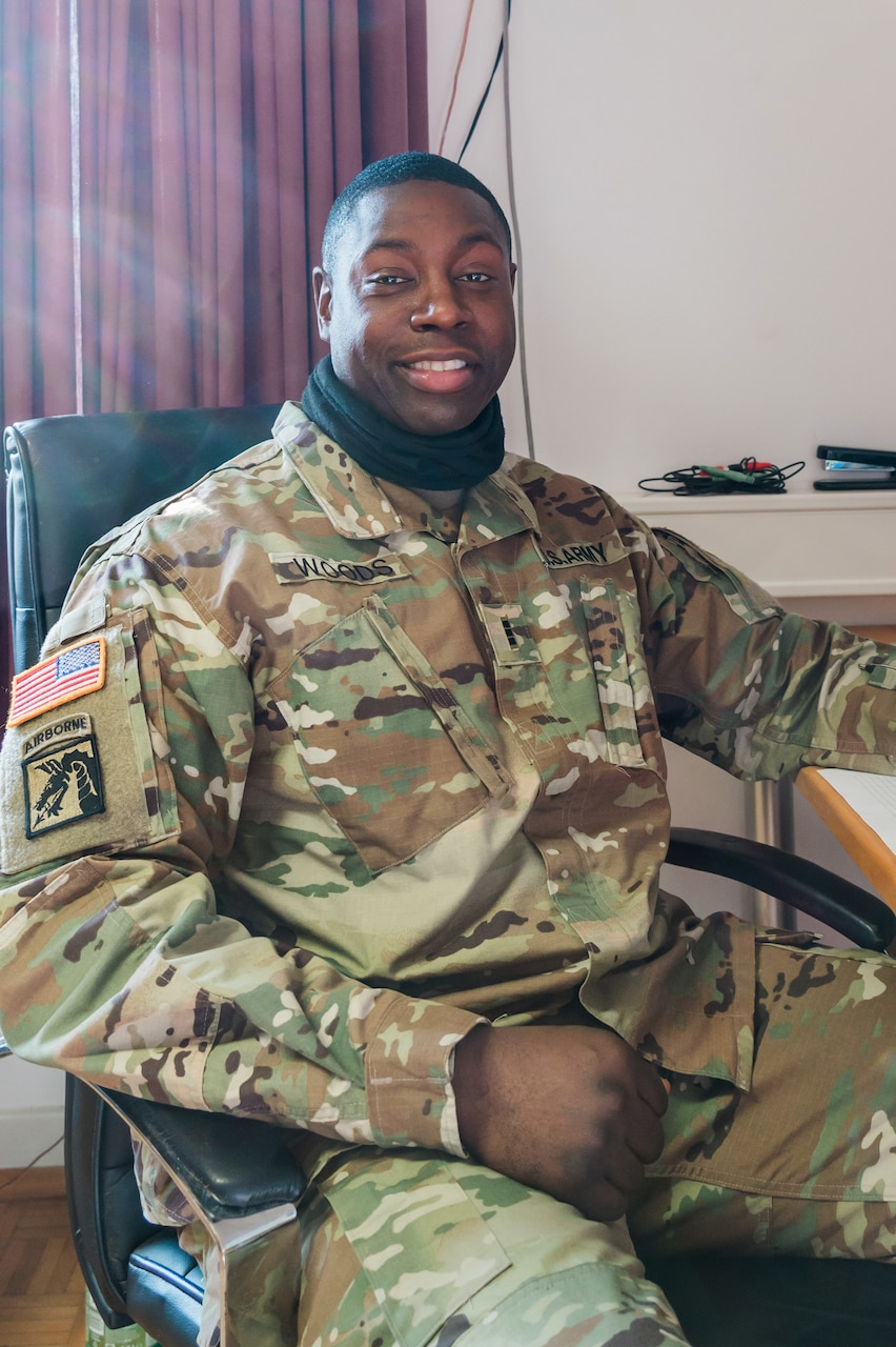 A seated soldier smiles for the camera.
