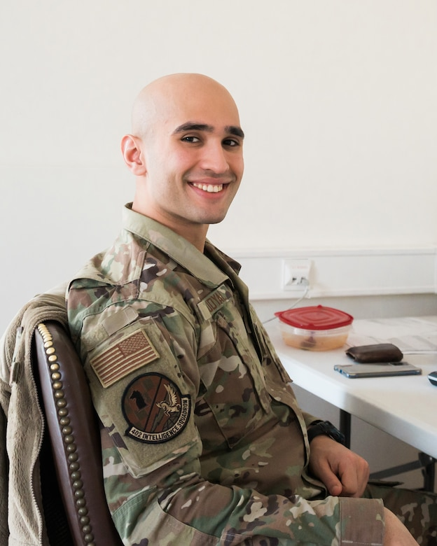 A seated airman smiles for the camera.