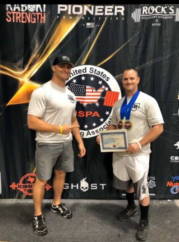 Master Sgt. Daniel Bedford (right), Air Force Recruiting Service National Events program manager and Senior Master Sgt. Michael Lear, AFRS Strategic Marketing Division superintendent, show off Bedford's two gold medals he won at the USPA (United State Powerlifting Association) 2020 Texas State Bench Press Championship and the USPA Military National Bench Press Championship.