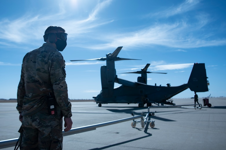 An Airman stands on the left as he fuels a CV-22 Osprey