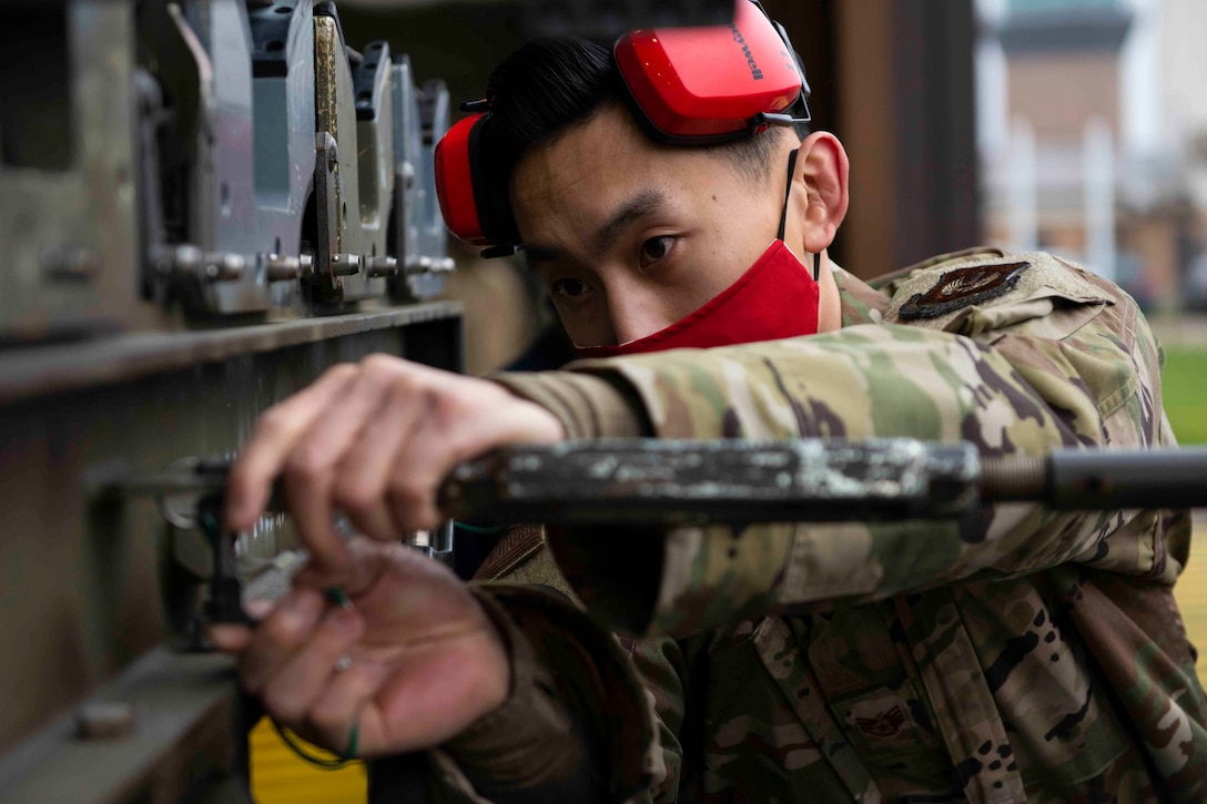 An airman wearing a face mask inspects a bomb rack.